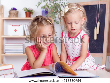 Two little sisters reading a book at the table - stock photo