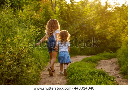 Two little sisters running on the road in the park on a sunny summer day. Family time. Cute babies. - stock photo