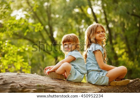 Two little sisters sitting back to back on a fallen tree. Park on a sunny summer day. Family time. cute babies - stock photo