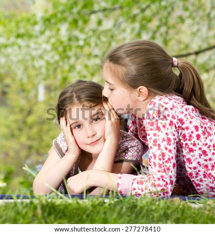 Two little sisters spending time together in spring day - stock photo