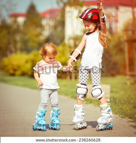 two little sisters to roller skate on the street - stock photo