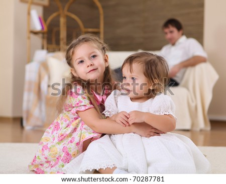 two little sisters together playing on the floor of a livingroom - stock photo