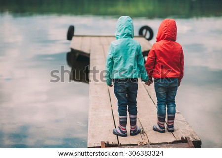 two little sisters, twins are on the Wooden bridge - stock photo