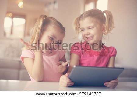 Two little sisters using tablet at home. Watching something funny.