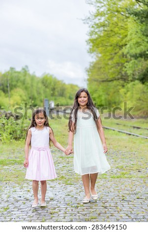 two little sisters walking hand in hand next to a train rail - stock photo