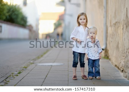 Two little sisters walking together outdoors
