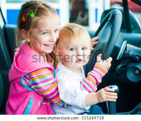 two little sisters while driving - stock photo