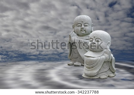 Two little smiling Buddha praying on a dreamy blue realm. - stock photo