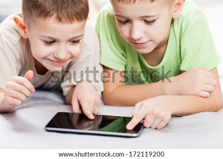 Two little smiling child boy brothers playing games or surfing internet on digital tablet computer - stock photo