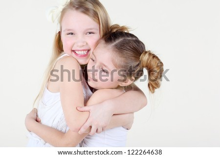 Two little smiling girl in clean white clothes hugged strongly.