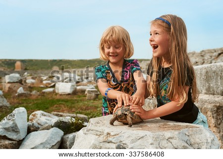 Two little smiling girls play with turtle