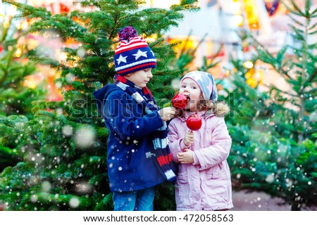 Two little smiling kids, boy and girl eating crystalized sugared apple on German Christmas market. Happy children in winter clothes with lights on background. Family, tradition, holiday concept