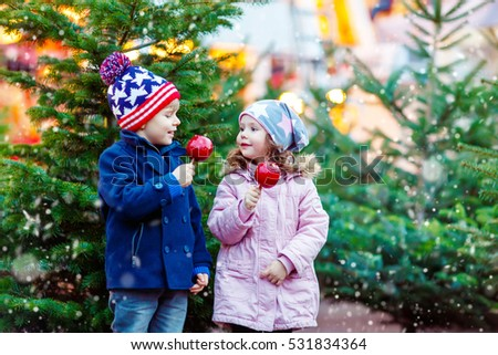 Two little smiling kids, boy and girl eating crystalized sugared apple on German Christmas market. Happy friends in winter clothes with lights on background. Family, tradition, holiday concept