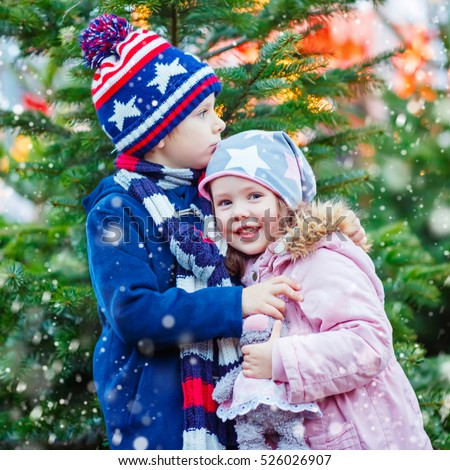 Two little smiling kids, boy and girl eating sugared apple on Christmas market. Happy children in winter fashion clothes with lights on background. Funny sister and brother