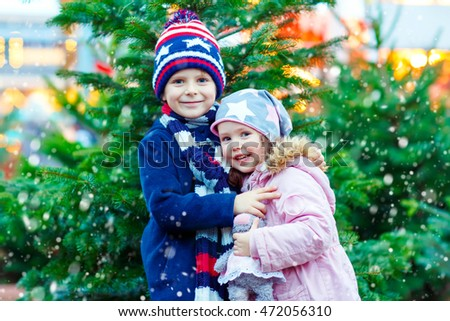 Two little smiling kids, boy and girl with christmas tree. Happy children in winter clothes on Christmas market with lights on background. Brother and sister together. Family, tradition, holiday