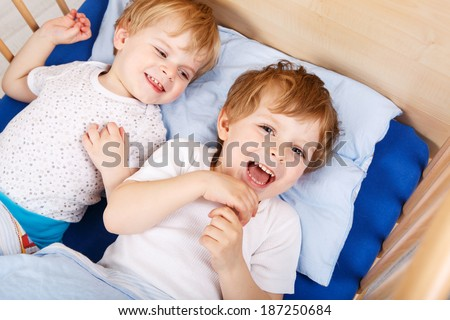 Two little toddler boys having fun and fighting together in bed before sleeping, indoors - stock photo