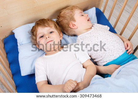 Two little toddler boys having fun in bed before sleeping. Family, childhood, siblings, love concept. - stock photo