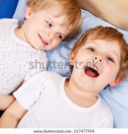 Two little toddler boys having fun in bed before sleeping.  Square size.