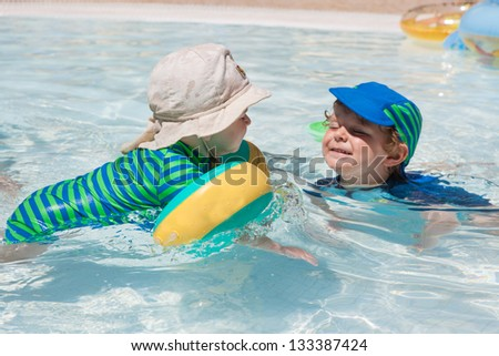 Two little toddler boys playing in the pool with water. Outdoor, summer.