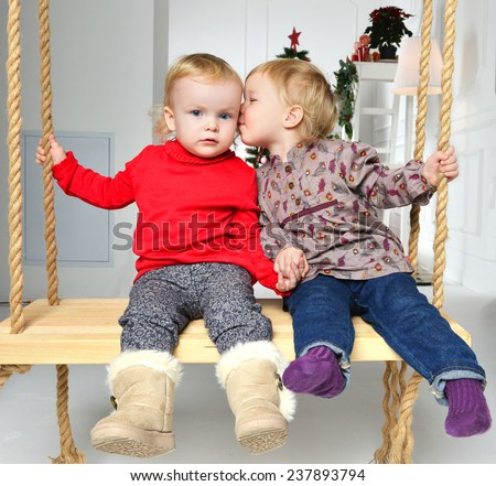 Two little toddler child kids girls sisters having fun on a swing kissing on a christmas new year tree background - stock photo