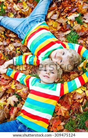 Two little twin boys lying in autumn leaves in colorful clothing. Happy siblings having fun in autumn park on warm day. Family, childhood, love concept. - stock photo