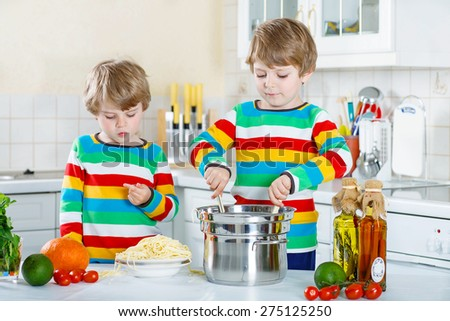 Two little twin kids having fun with cooking of spaghetti and fresh vegetables in domestic kitchen, indoors. Sibling children in colorful shirts. - stock photo