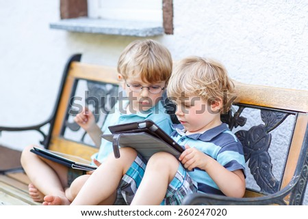 Two little twins boys playing with tablet pc, outdoors. Kids playing together, learning and having fun. - stock photo