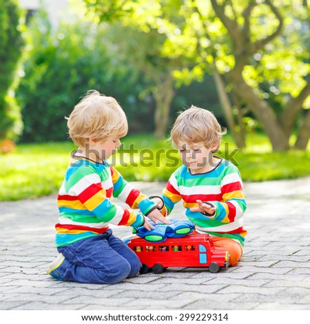Two little twins in colorful clothing with stripes playing with red school bus and toys in summer garden on warm sunny day. Learning to play and communicate together. - stock photo