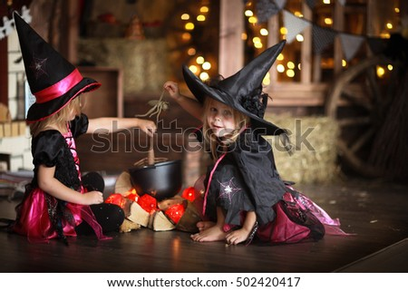 Two little witches in costumes and hats conjure above pot, childhood halloween, dark background