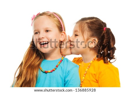 Two little 6-7 years old Asian and Caucasian girls with pile of books gossip about something funny smiling and laughing, isolated on white