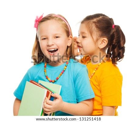 Two little 6-7 years old Asian and Caucasian girls with pile of books gossip telling funny secret, isolated on white - stock photo