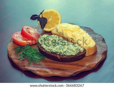 two loaves of bread with butter and dill, tomatoes, lemon, food, close-up, vintage, retro style