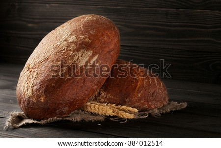 Two loaves of fresh rye bread with ears of wheat close-up on a dark wooden background with copy space