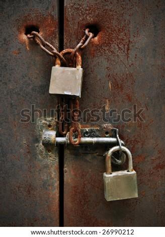 two lock on rusty iron door - stock photo