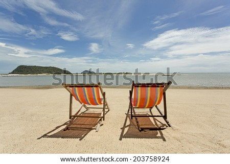 Two lone deck chairs looking out to see on a beautiful sunny day on a sandy beach