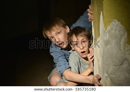 Two lonely little boys sitting in a dark cellar