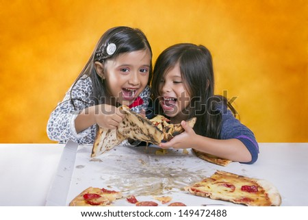 Two long-haired girls dressed in sweater Smiling while trying to eat a pizza - stock photo