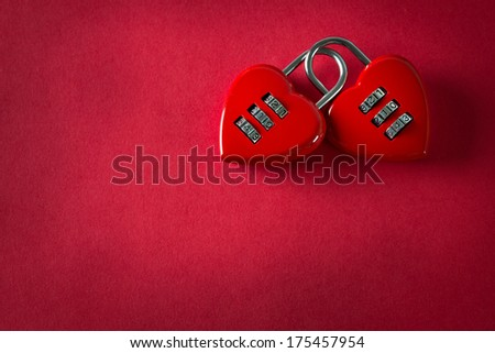 Two love combination padlock bonded together in red background - stock photo