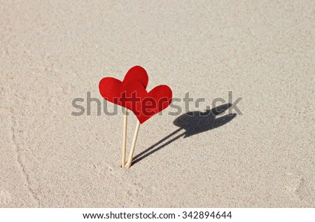 Two love hearts on beach. Red paper heart signs on beige seaside sand. Romantic seaside getaway moment background - stock photo