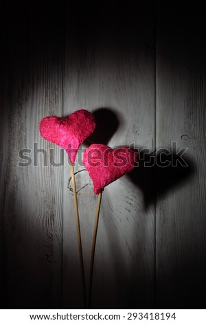 Two love hearts on wooden background in the dark - stock photo