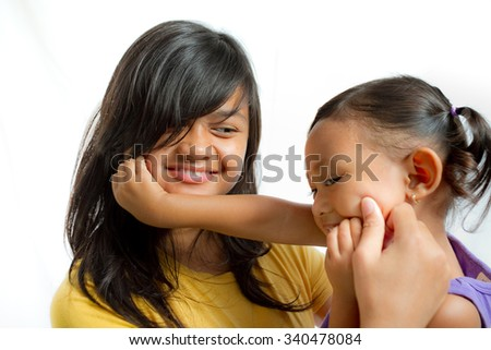 Two lovely Asian sisters playing together - stock photo