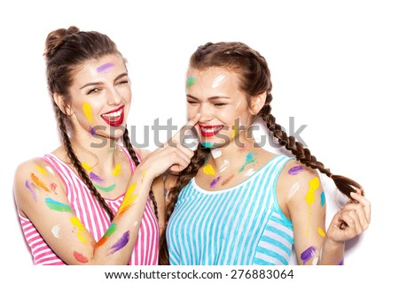 Two lovely girl friends hugging and having fun. Women smeared in paint. White background not isolated - stock photo