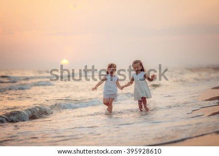 two lovely girls in white dresses walking on the beach at sunset - stock photo