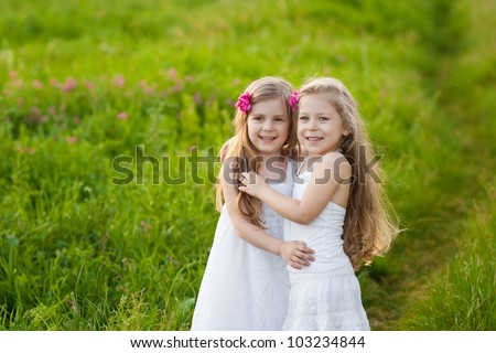 Two lovely girls playing on meadow - stock photo