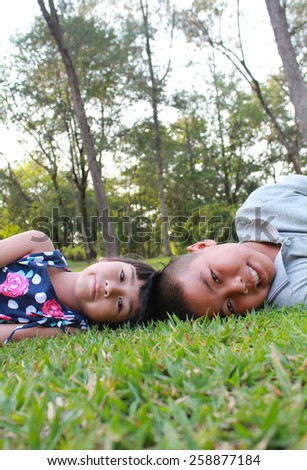 Two lovely kids with green grass background. - stock photo