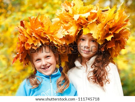 Two lovely little friends in autumnal headwreaths - stock photo