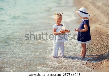 Two lovely little girls in clothes in a marine style walking barefoot on the waves along the beach on a summer sunny day. Holiday on a seashore. Sea. Ocean. Friendship. - stock photo