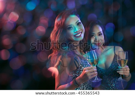 Two lovely Vietnamese girls with champagne glasses