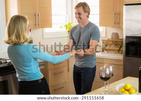 Two lovers dancing holding hands celebrating their relationship and learning to teach how to dance - stock photo