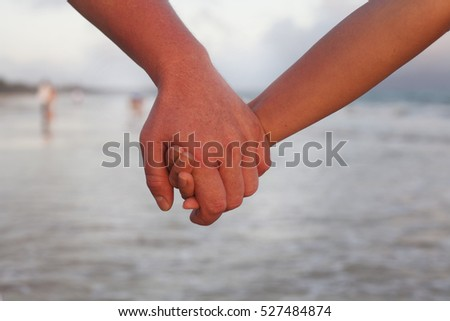 two lovers walking hand to hand on the beach at sunset time. Close-up.